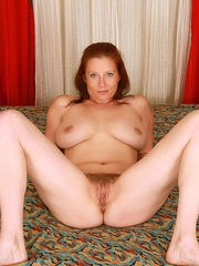 Amateur cougar with medium-sized boobs spreads legs shows off her hairy snatch