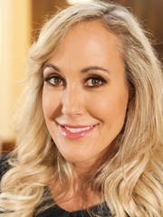 Older blonde woman Brandi Love unveils her large breasts while undressing