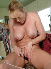 Blonde mature woman Bethany Sweet takes off her dress and dildos her snatch