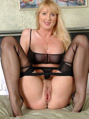 Alluring mature woman in nylon stockings toys her hairless twat with a red toy
