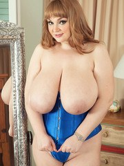 Chubby Euro female Micky Bells fondles her giant breasts wearing a blue corset