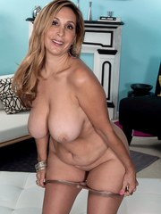 Middle aged blonde Sophia Jewel gets rid of pink dress and hose to pose naked