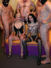 Blonde and brunette sluts take on a crowd of men in a group sex setting