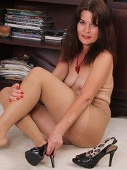 Older brunette completes her undressing with hose and heels removal