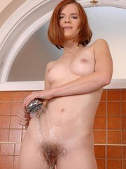 Redhead chick Denisa dries off her wet beaver with blow dryer after a bath