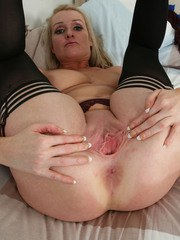 Mature woman with big boobs shows off her wide open snatch in sexy stockings