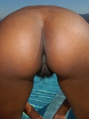 Black amateur Nina shows her hairy bush off beside a swimming pool