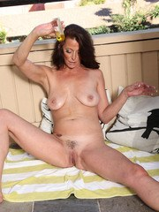 Mature woman Mimi Moore rubs oil into her trimmed pussy after a striptease