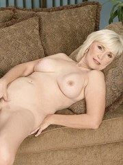 Older woman Lola Lee toys her pussy after getting naked on her couch