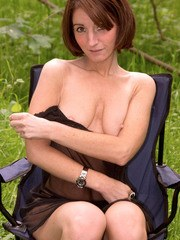 Solo model Kaye bares her small tits and bald pussy in grassy meadow