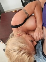 Older blond secretary Charity Mclain greets her boss with a titjob and blowjob