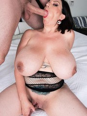 Brunette female Paige Turner holds her monster tits while sucking a huge cock