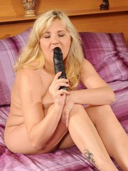 Mature blonde woman removes lingerie before toying her twat with a black dildo