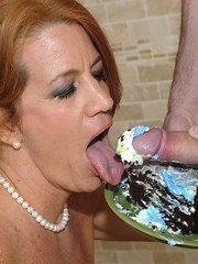 Older redheaded MILF licks whip cream off a cock until it blows a load of jizz