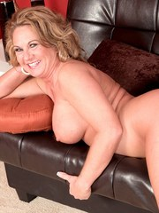 Sexy mature lady Cali Houston sticks her fingers in her pussy after undressing