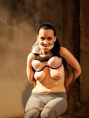 Gagged brunette female has her breasts nearly cut in two by rope restraints