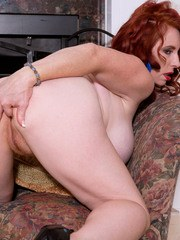 Middle-aged redhead Red Vixen frees her huge boobs before showing her snatch