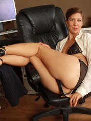 Older businesswoman in glasses bares her beaver after stripping in her office