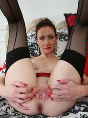 Clothed older woman casts her red dress aside to pose nude in garters and hise