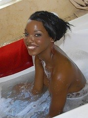 Black girl Kim Kandy puts her hair up before oral sex in the bathtub