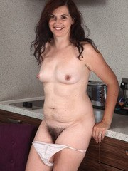 Mature brunette with a couple of extra pounds undresses to show her hairy bush