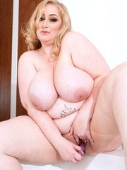 Obese blonde chick sheds her lingerie before toying her pussy