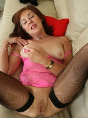 Older lady in black nylons and boots slides her pink onesie aside on sofa