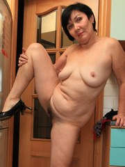 Overweight mature woman cant resist playing with her bush in the kitchen