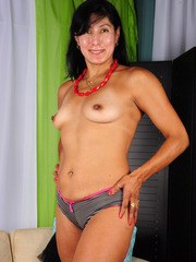 Mature Latina lady uncovers her tiny tits as she strips naked