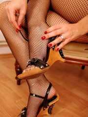 Hot solo model rolls off her mesh pantyhose after unbuckling her heels