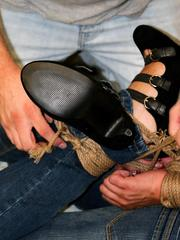 Clothed female with dark hair struggles against her rope restraints