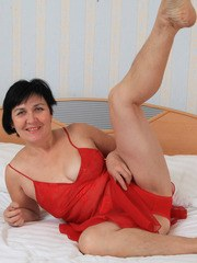 Mature woman Yulya removes her red lingerie to show off her hairy vagina