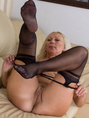 Older blonde woman shows strips off her pink dress and crotchless hose