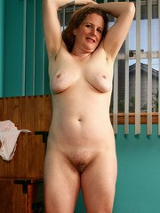 Chubby mature woman parts her hairy pussy after undressing in her bedroom