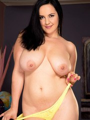 Dark haired chick Roxanne Diamond uncovers her big tits as she undresses