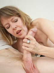 Topless older lady Jamie Foster jerks off a guy with a massive cock