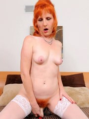 Older redhead inserts a sex toy into her hairy ginger pussy