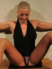 Submissive female is gagged and chained to a wall before force masturbation