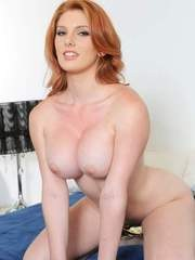 Redhead solo model Lilith Lust flaunts her big boobs as she gets undressed