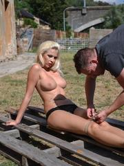 Topless blonde chick allows herself to be tied to a pallet in backyard