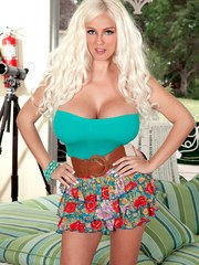 Blonde solo girl Dolly Delight exposes her hooters as she gets undressed