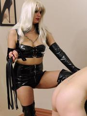Latex attired Domme abuse her female sex slave with a flogger and strapon cock