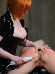 Clothed redhead female tortures her blonde slave with electro device