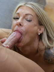 Blonde chick with a tattoo sleeve gives a blowjob in black stockings only