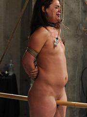 Middle-aged female undergoes a painful torture session in a dungeon
