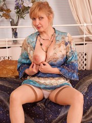 Older lady uncovers her nice boobs before masturbating in tan stockings