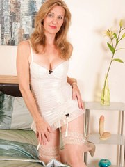 Mature lady in lingerie and tan nylons rids her dildo atop her bed