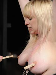 Busty female undergoes nipple torture and forced masturbation by a Domme