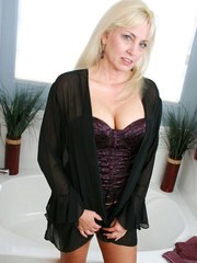 Older blonde woman Cala Craves unleashes her nice melons before finger fucking