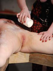Clothed female with dark hair tortures a restrained woman with hot wax
